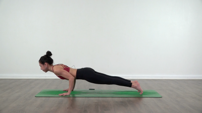 Lizette is practising yoga on a green yoga mat chaturanga