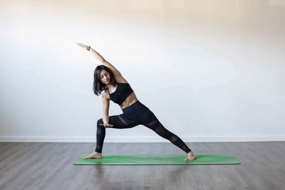 Extended side angle pose with Female yogi on green yoga mat