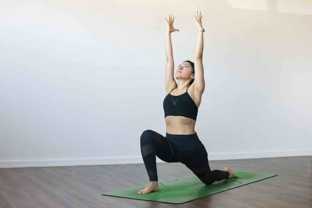 Low lunge pose  with Female yogi on green yoga mat